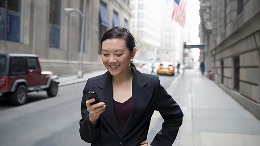 一位商务女性正在手机上查看自己的TD美元日常商业账户。
