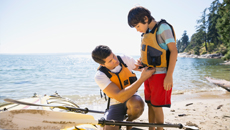 Father buckling son's life jacket on beach.