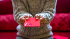 Hands holding Chinese red envelope.