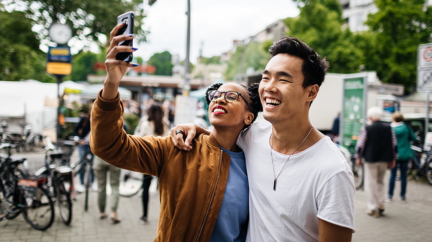 Man and woman taking a photo of themselves on a city sidewalk