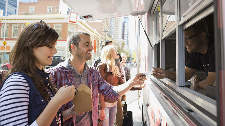 Man and woman getting food from a food truck.