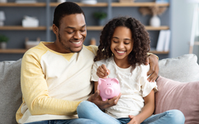 Father and daughter put money in piggy bank