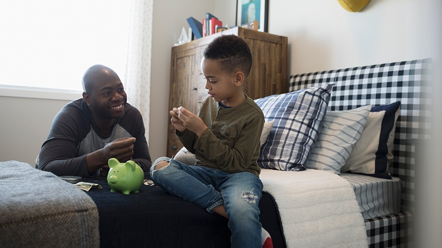 Father and son talking about money with a green piggy bank.