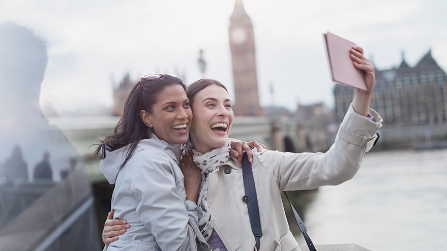 A smiling couple take a selfie with Big Ben in the distance.