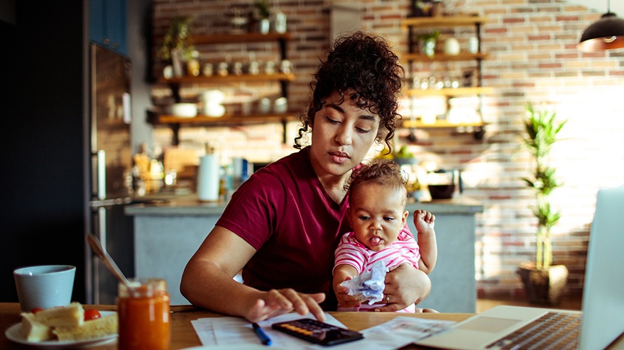 Sitting young mother holds infant daughter in a kitchen while going over her financial goals with a smartphone and laptop.