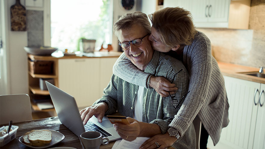 Smiling husband and wife in front of a laptop in a kitchen.