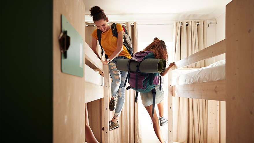 Two women climb bunkbeds in a dormitory-style room while wearing backpacks