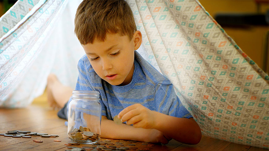 Boy learning financial literacy for kids by counting coins under a blanket tent