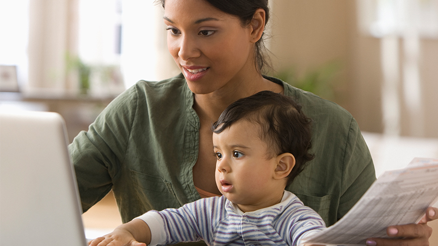 A woman holds papers and looks at a computer screen while a baby sits on her lap.