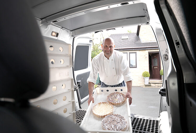 A bakery owner removes cakes from the back of his van.