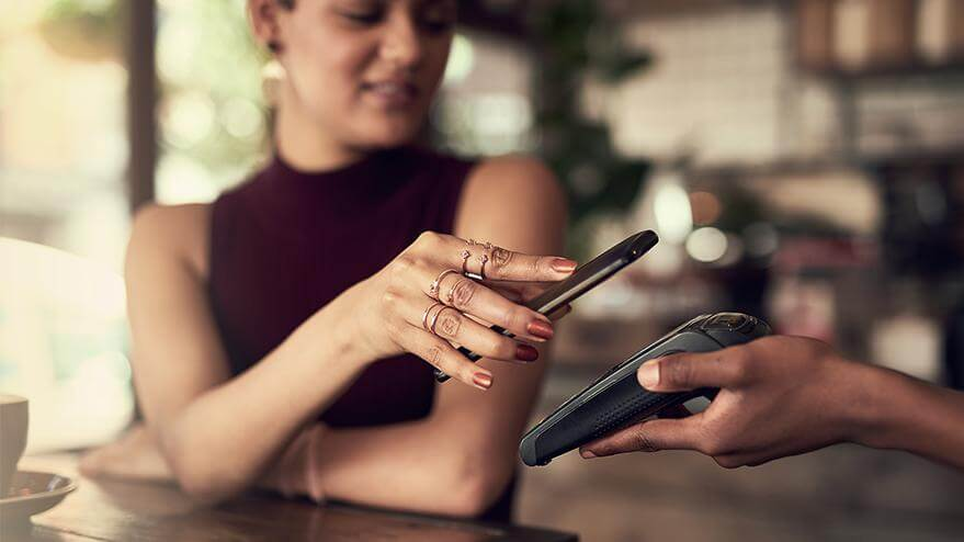 A woman in a café paying for her purchase with a smartphone