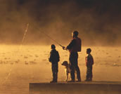 Father and children fishing on a dock at sunrise.