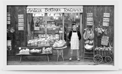 Image of man standing proudly in front of his store