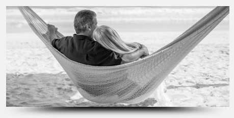 Image of couple resting on a hammock on the beach