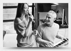 Image of woman singing and man on keyboard