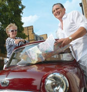 Vacationing couple reading a road map over hood of vintage car